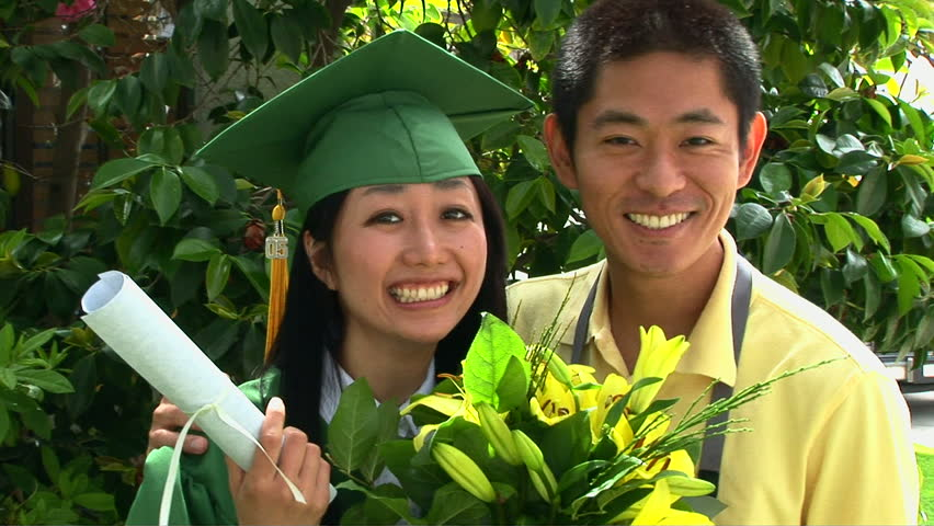 Young Asian woman in graduation gown with boyfriend outside