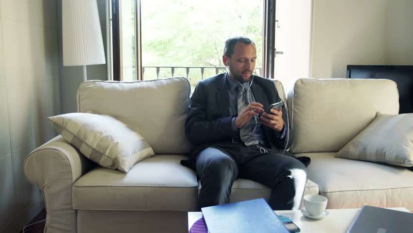 Businessman listening to music on cellphone and sitting on sofa at home  | Shutterstock HD Video #8864326