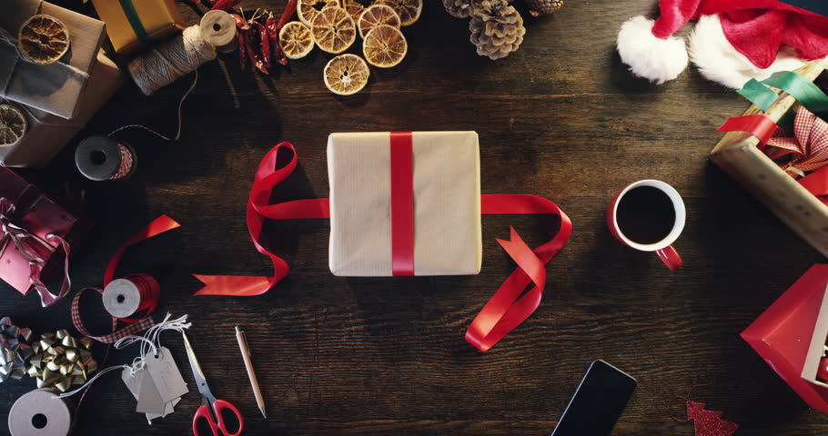 Top view woman wrapping christmas presents at wooden desk hands from above - Red Epic Dragon