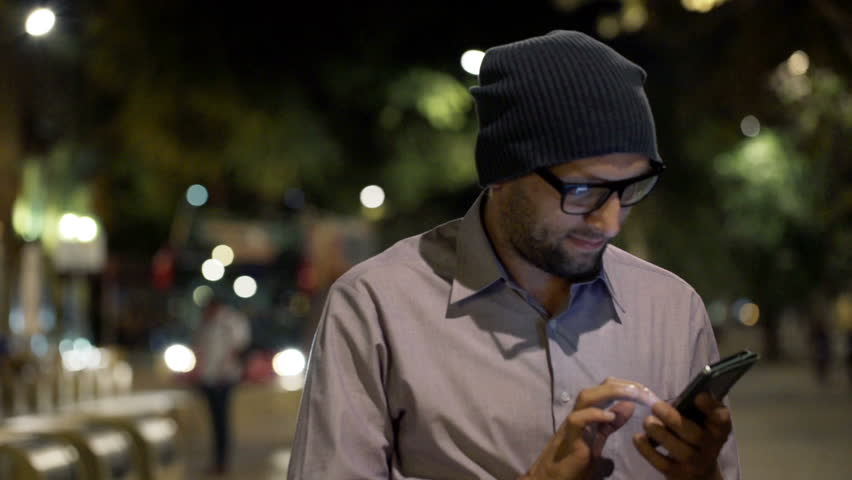Young, trendy man standing with smartphone in the city 