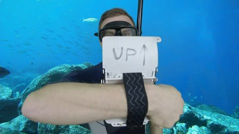 Diving sign- divemaster  writes on the plate and shows ok sign GO UP, ASCENT 1 of 4 also a available on the green screen all of diving signs from course