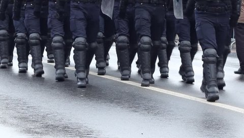 Heavily armored policemen with shields, bats, boots walking in disclpine on a riot public intervention.