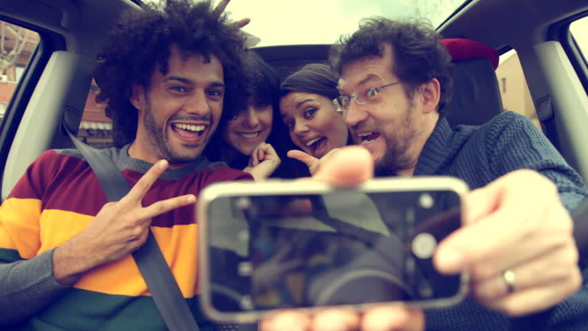 Four cool people in car taking selfie with smartphone smiling happy