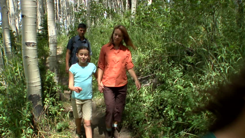 Family Hikes On Forest Trail And Waves To Passerby