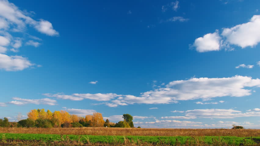 White clouds flying on blue sky over autumn forest and field - Countryside landscape time-lapse