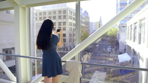 Teen Takes A Photo Of City Below Her, From A Skybridge (Lens Flare)