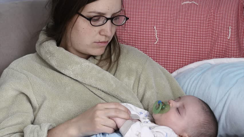 A sleepy and tired young mother rocking her newborn baby boy to sleep after nursing him | Shutterstock HD Video #9015046