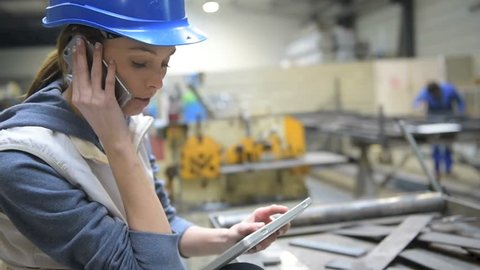 Woman engineer in factory talking on mobile phone