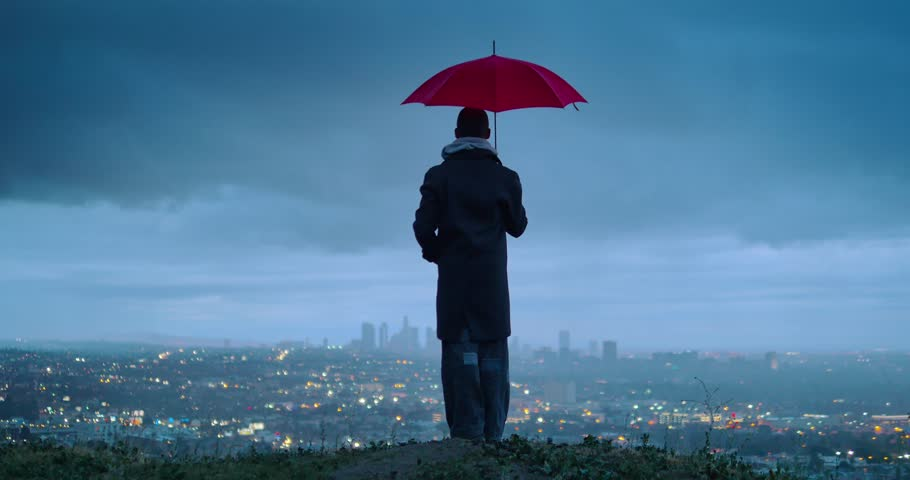 Man under red umbrella overlooking cloudy Los Angeles cityscape from Hollywood Hills at twilight. 4K UHD.