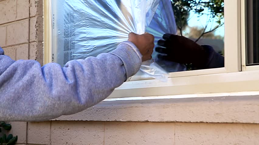 painting house exterior. Professionals construction workers are painting the exterior of house  In this video is shown Handsome Young Man On Ladder Painting House Exterior With Paint