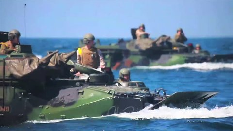 CIRCA 2010s - Amphibious assault vehicle tanks leave a Navy vessel during a wartime exercise.