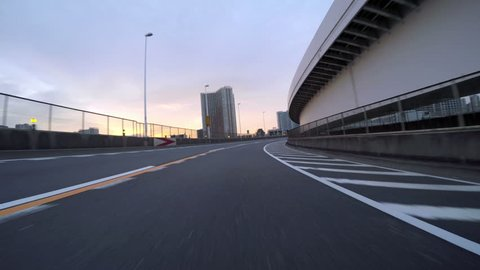 Driver POV over Tokyo Rainbow Bridge's empty lower deck at sunset. Climbing the loop through the city buildings and Tokyo Bay.