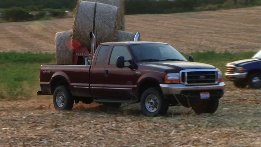 Trucks hauling round hay bales out of field - audio from external microphone.