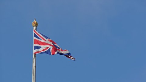 The England flag waving on the pole. It waves on the breeze of the wind on the Buckingham Palace