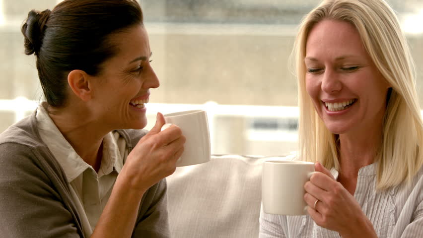 In slow motion two friends sitting on the couch chatting over coffee at home in sitting room | Shutterstock HD Video #9153086