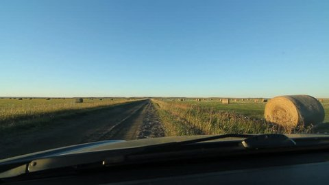 Driving on farm road with hay bales. Stopping by side of road. Saskatchewan, Canada