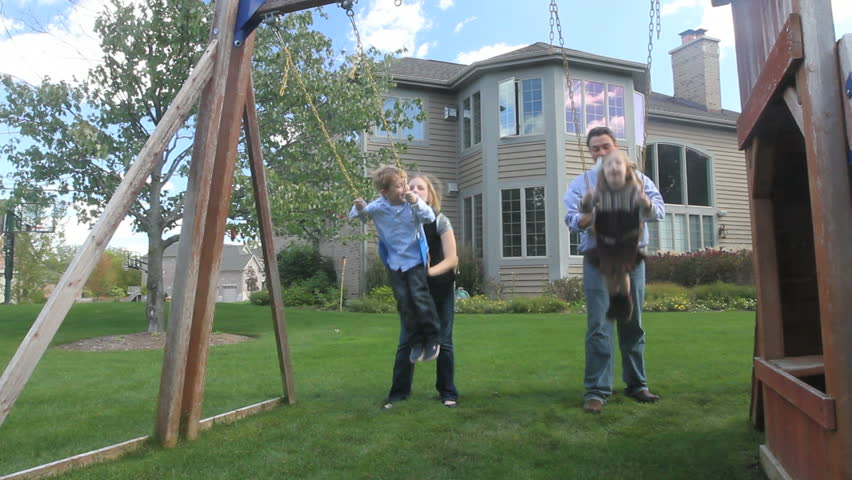 A father and mother push their two kids on the swings in the back yard of their luxury home
