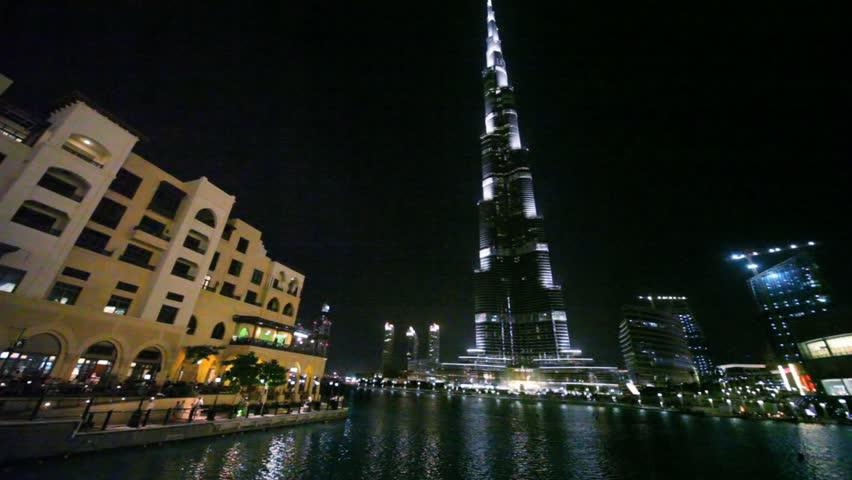 DUBAI, UNITED ARAB EMIRATES - APRIL 13: People walking at night in Dubai near the trade center Souk Al Bahar and skyscraper Burj Khalifa on April 13,2010. Burj Khalifa is the tallest man-made structure ever built, standing at 828 m (2,717 ft).