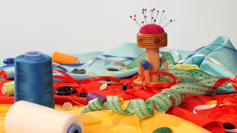 Different colors like white, blue and green threads, needles in pincushion, meter, ribbons and buttons on bright blue, yellow and red clothes on white background, rotation