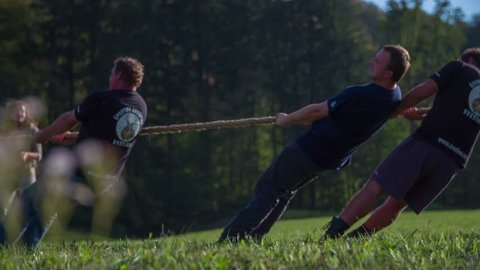 SENTJUR, SLOVENIA - OCTOBER 2014: Black team giving there best in tug war. Close up footage of a tug war black team giving there bast in tug war in the middle of country side on sunny summer day