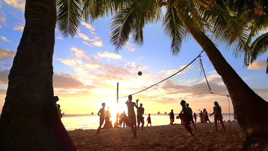 Slow motion. Sunset silhouette of people playing volleyball at tropical beach under palm trees. Boracay island, Philippines summer vacation