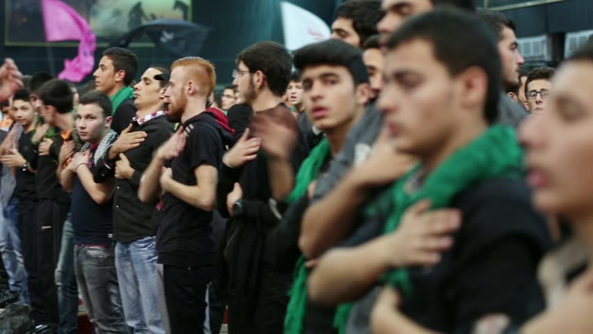 BEIRUT'S SOUTHERN SUBURBS, LEBANON - 2014: Young men lament for Imam Hussein's calamity. Scene from the revival of Ashura 2014 hosted by Hezbollah on the occasion of the martyrdom of Imam Hussein