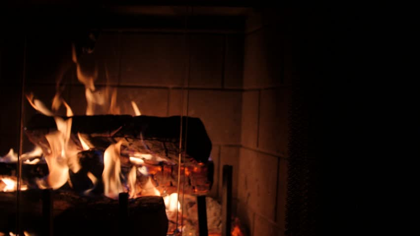 A Jib Shot Of Wood Burning Fireplace At Night In The Living Room