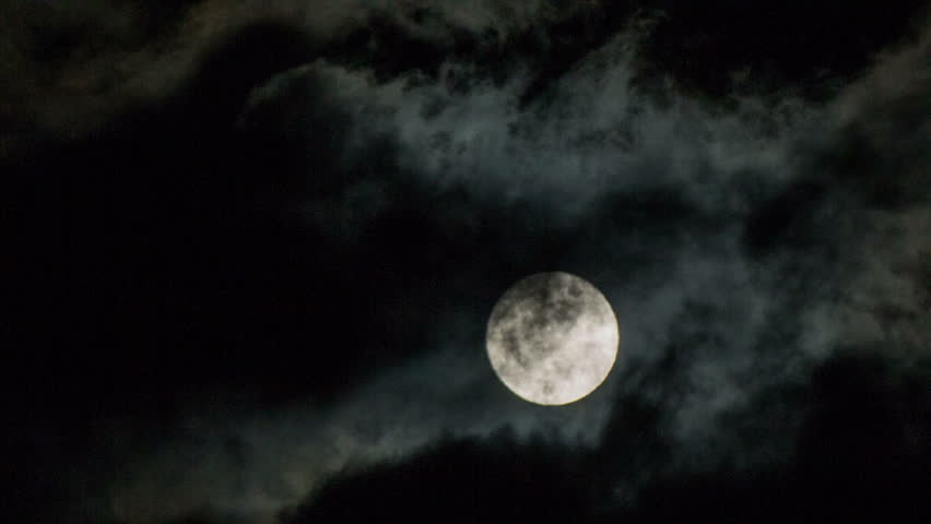 Moon behind the clouds at night close up.Night shot of cloudy weather and fool moon bright in the sky.