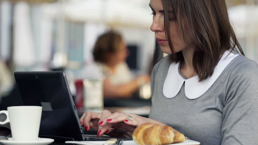 Young, attractive businesswoman working on laptop, sitting in cafe     Shutterstock HD Video #9315962