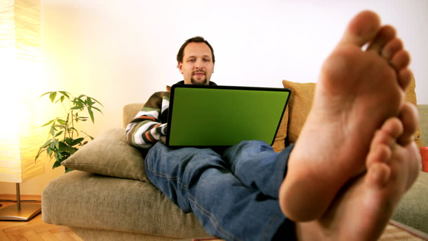 Man on sofa working on laptop barefoot