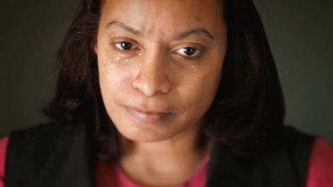 Black African American ethnic woman crying looking at camera