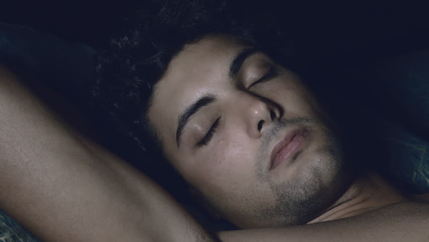 thoughtful young man shirtless opening eyes in bed: