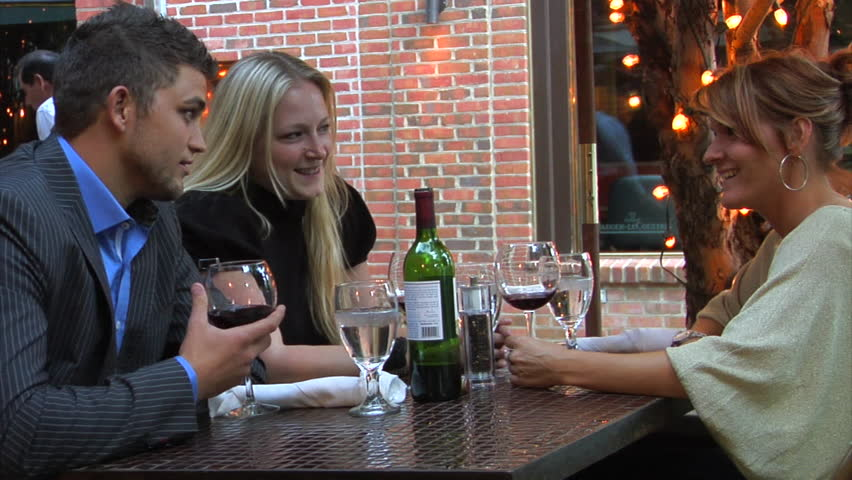 Three friends eating, drinking and having a good time at outdoor restaurant. | Shutterstock HD Video #9338276