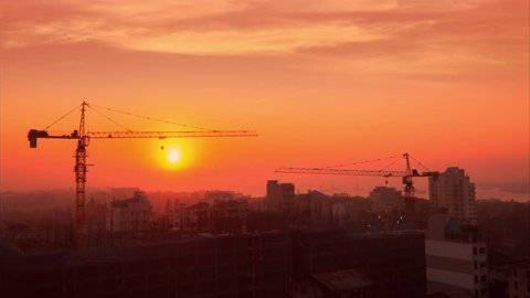 Time lapse aerial cityscape view of crane silhouette working at building construction near the harbor at sunrise. Yangon, Myanmar (Burma) travel landscapes and destinations