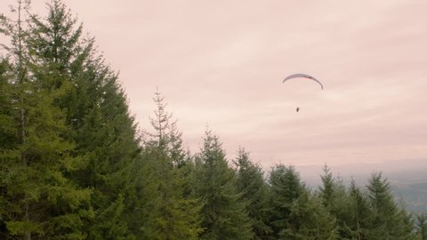 Paragliding above trees and a pink evening sky. The paraglider soars through the air while doing an exhilarating extreme outdoor adventure sport.