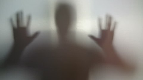 Silhouette of mad man against wall, schizophrenia, addiction. Male ghost shadow with scary hands up looking through glass, thriller. Aggressive maniac following victim, hopelessness, strange nightmare