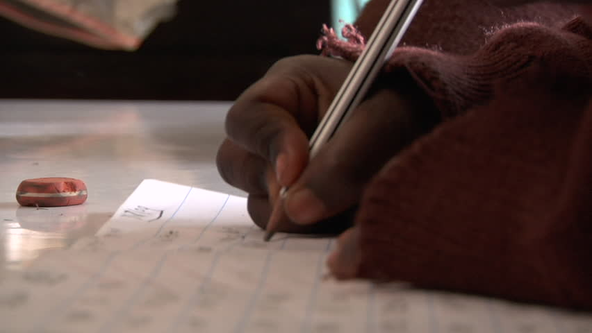 Close shot of a child writing and erasing on loose-leaf paper. Shot in Kenya in high definition.