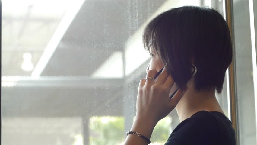 Asian woman standing in front of a glass door and talking on mobile smartphone    Shutterstock HD Video #9409736