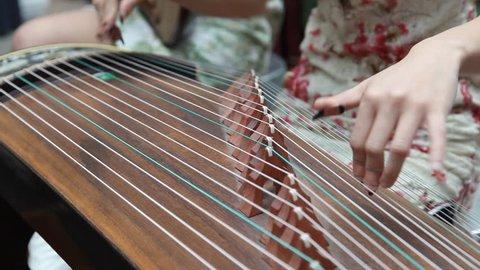 Chinese girl wearing a cheongsam playing the national instrument - Guzheng