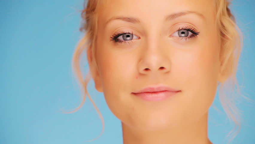 Smiling woman, close-up on blue background