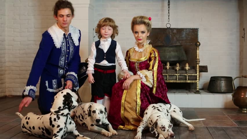 Young father, mother and little son in medieval costume stand near fireplace with three dalmatians on leashes