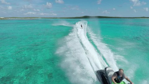 Aerial view of a man water skiing being pulled by a Jetski over crystal clear, tropical waters