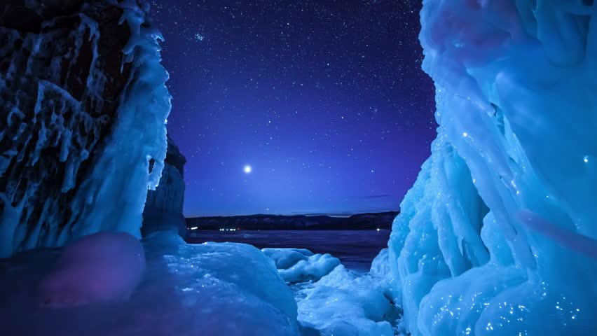 Rotating stars and north light above frozen lake. 4k timelapse