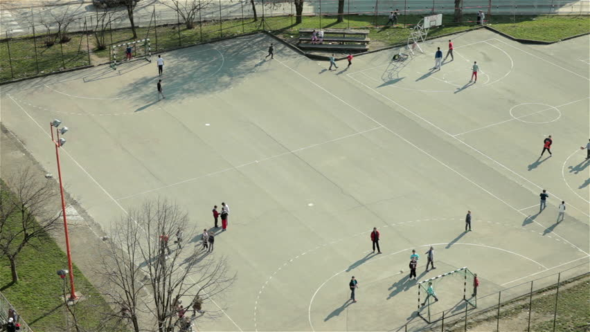 Group of children playing game with ball on school playground. Boys playing football and basketball on sport court. Kids training on school yard. Recreation,leisure time,soccer,sunny day,high angle.