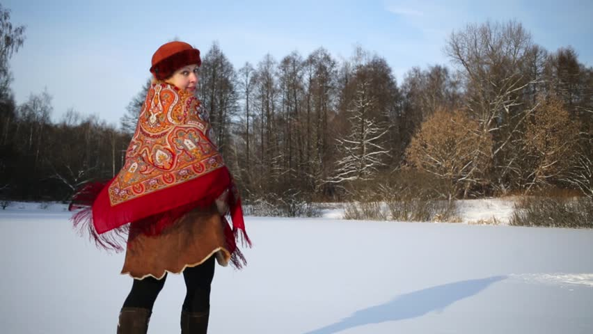 Young woman in sheepskin short fur coat with colored shawl runs through snowy glade and dances spinning round herself.