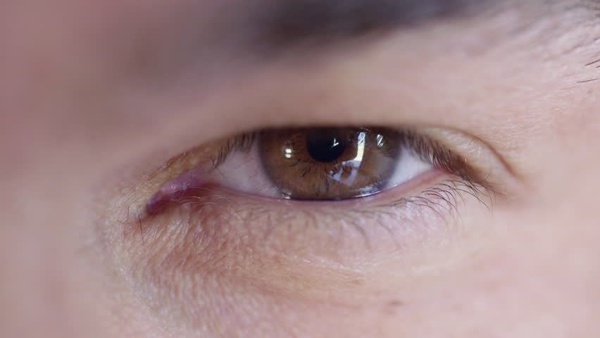 Big close up of a man's brown eye looking at the camera and looking around.  Recorded in 4K.