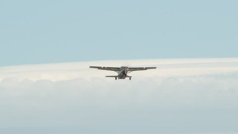 Small airplane taking off from Portland International Airport with camera zoom out.