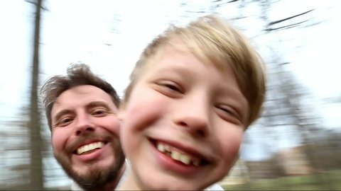 Father and son spinning around together while taking selfie in park. Point-of-view shot Funny family have fun outside. Happy dad and kid looking at camera. Smiling laughing man and child. Spring park
