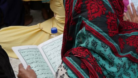 AJMER, INDIA - 30 OCTOBER 2014: An unidentified Muslim lady reads verses from the Quran during Muharram celebrations inside the Dargah shrine in Ajmer.