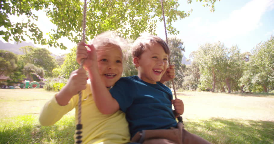 Working as a team, a little girl and boy having fun trying to swing really high in slow motion,